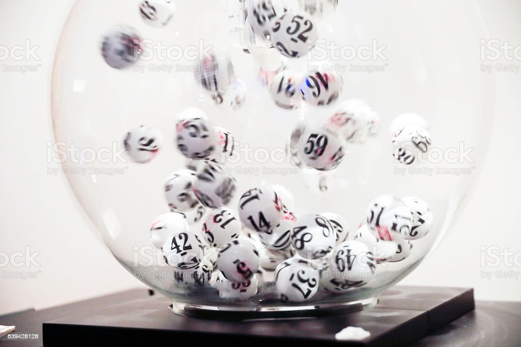 Lottery balls moving in glass sphere stock photo