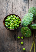 Lotus seeds in bowl and calyx on wood background