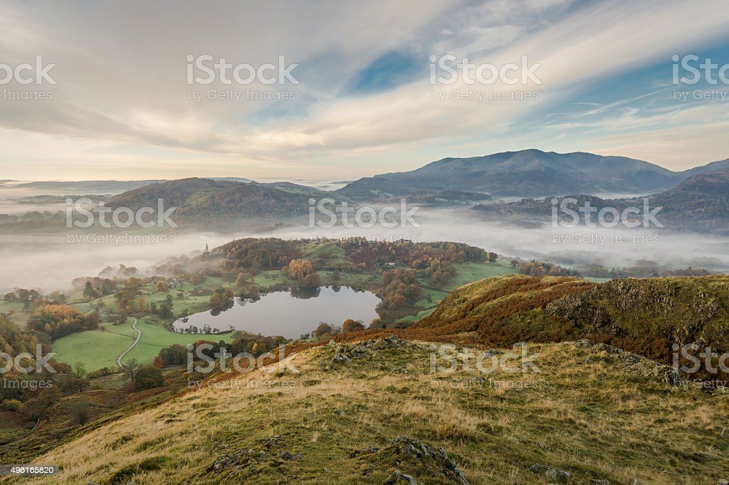 Loughrigg Tarn On A Autumn Foggy Morning With Beautiful Clouds. stock photo