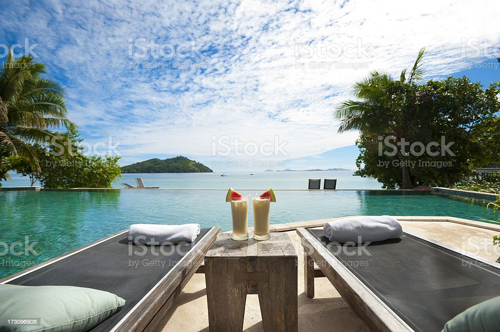 Sun lounges and cocktails by the pool stock photo