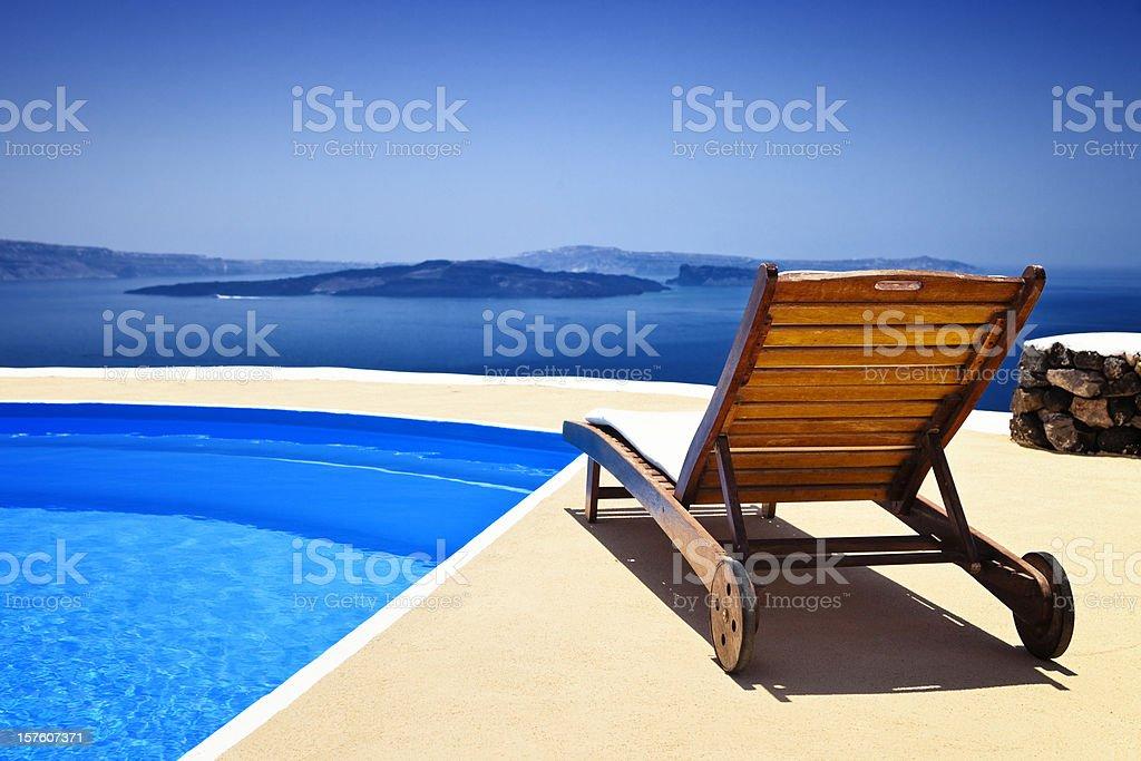 Lounge chair and pool over Santorini caldera stock photo