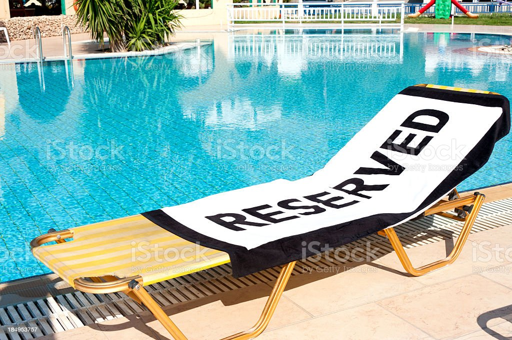 Lounge chair next to pool with 'Reserved' towel stock photo