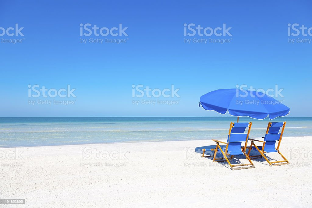Lounge Chairs and Umbrella at the Beach stock photo