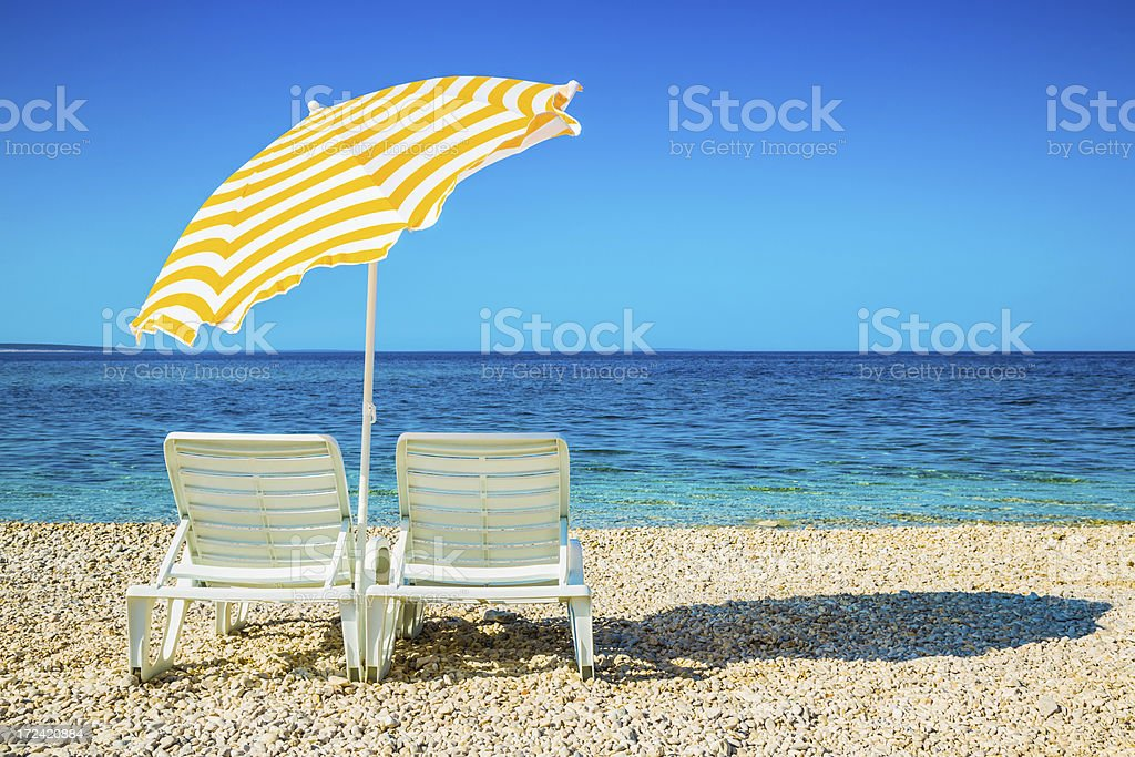 Lounge chairs and umbrella on beach stock photo