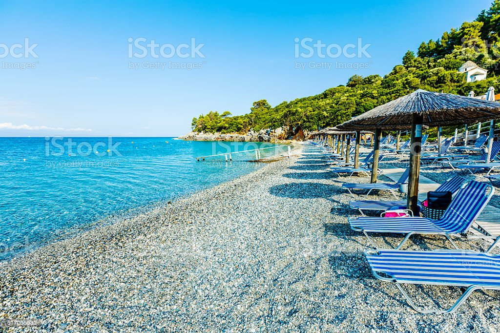 Lounge chairs and umbrella on private beach on Skopelos island stock photo