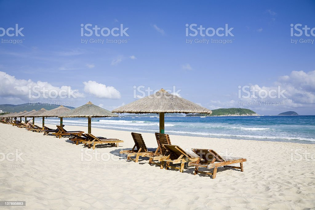 lounge chairs  and umbrellas by the sea royalty-free stock photo