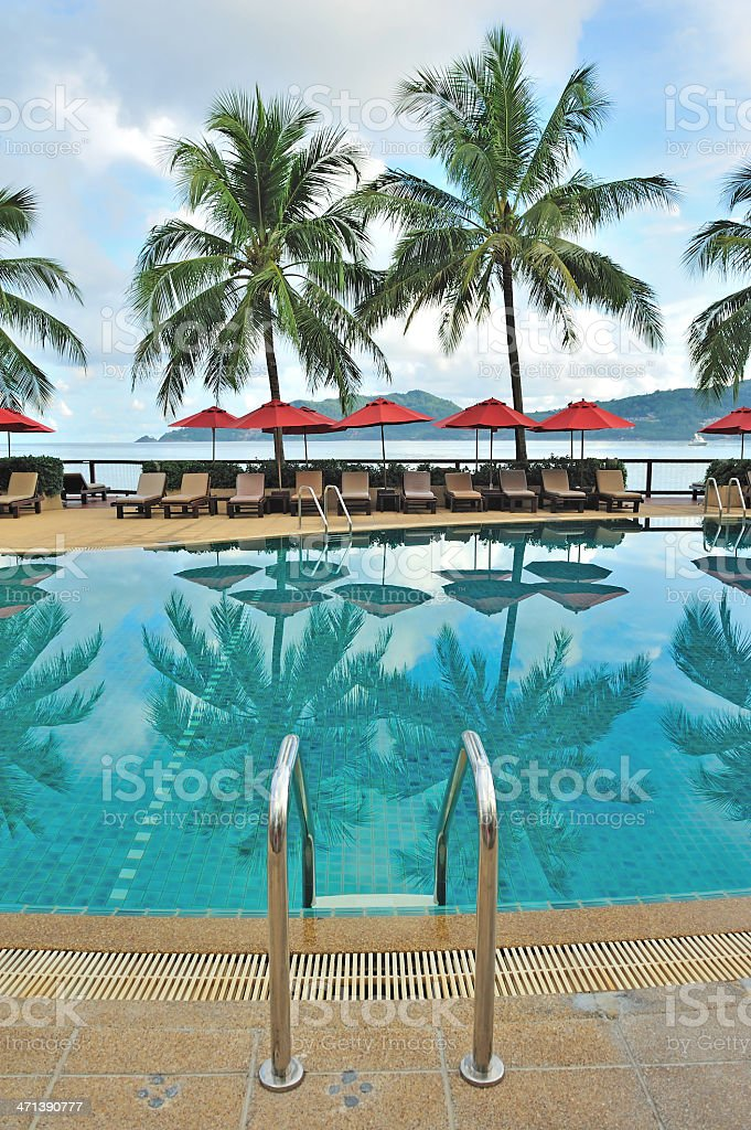 Lounge chairs and umbrellas poolside at a tropical resort royalty-free stock photo