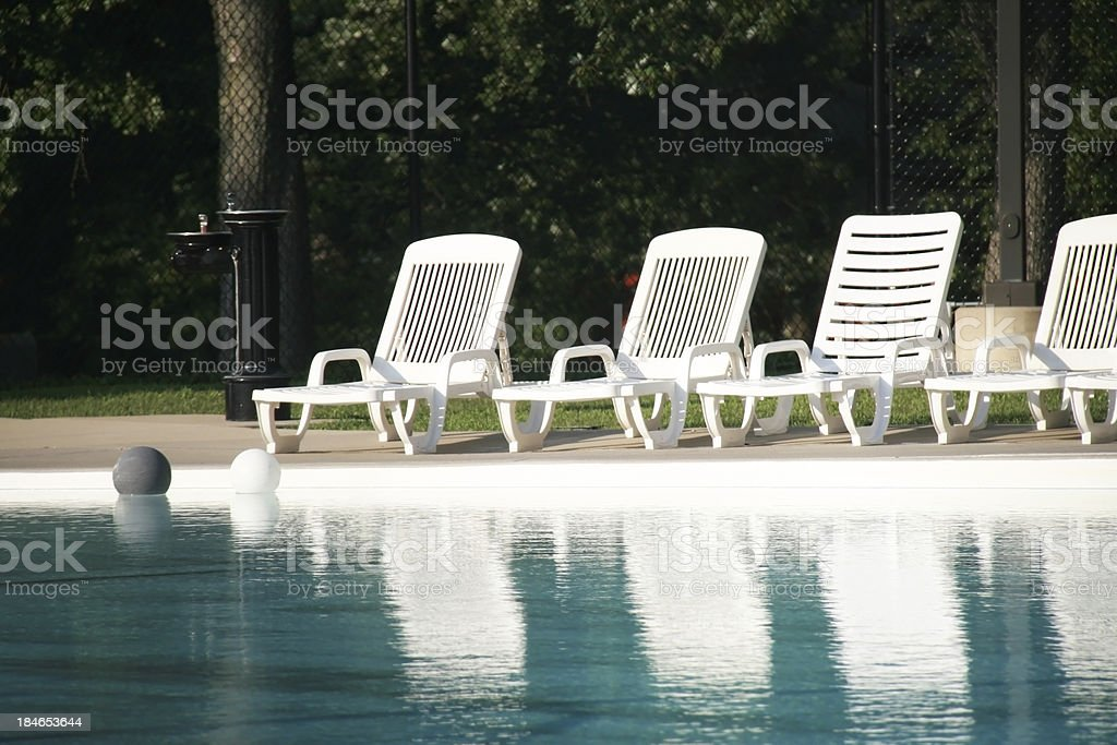 Lounge chairs at poolside.  Balls floating on water. royalty-free stock photo