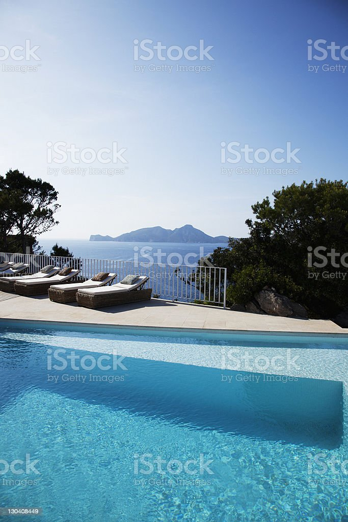 Lounge chairs beside pool on patio royalty-free stock photo