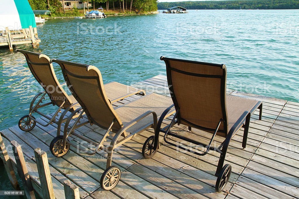Lounge chairs on a beautiful lake front dock stock photo