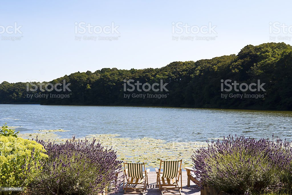 Lounge Chairs on a Deck at a Lake royalty-free stock photo