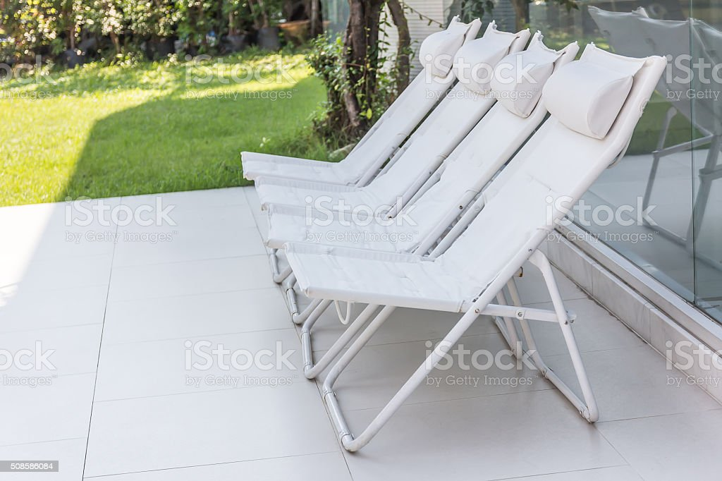 Lounge sunbeds near swimming pool, outdoor near sea stock photo