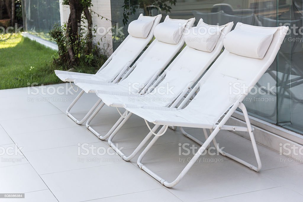 Lounge sunbeds near swimming pool, outdoor near sea stock photo