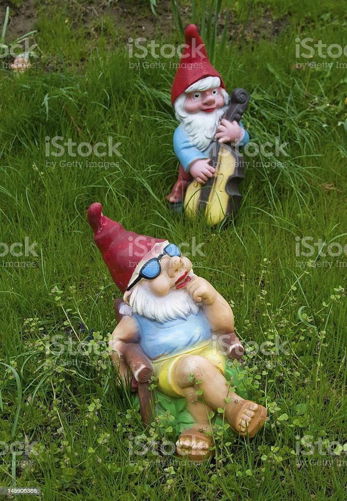 Lounging garden gnome statues in the grass stock photo