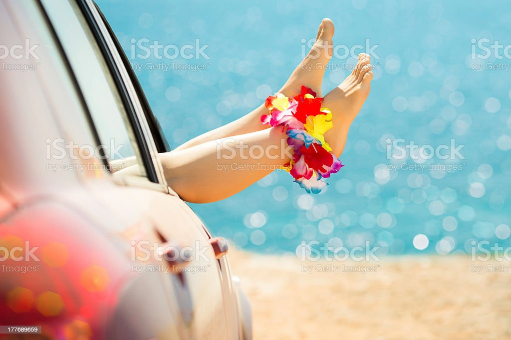 Lounging with feet out the window of a car parked at beach royalty-free stock photo