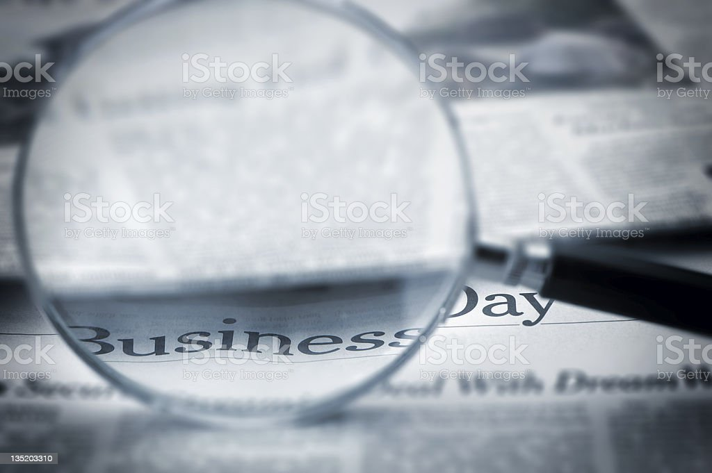 Loupe lies on the newspaper with title Business day royalty-free stock photo