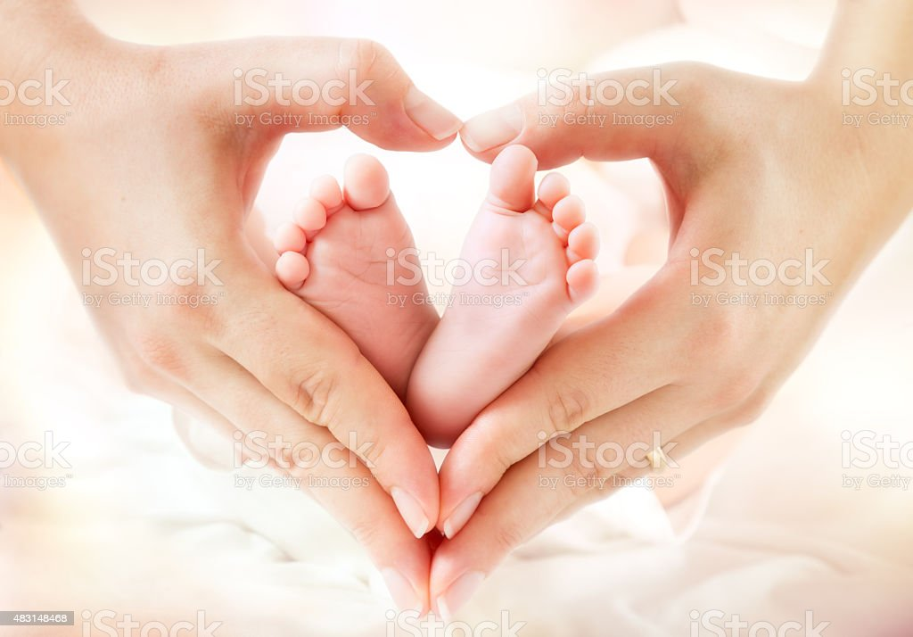 love and childhood - newborn feet in mom hands stock photo