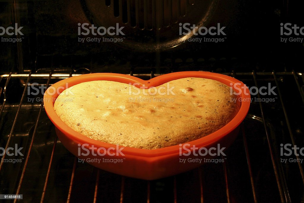 Love cake rising in the oven (2) stock photo