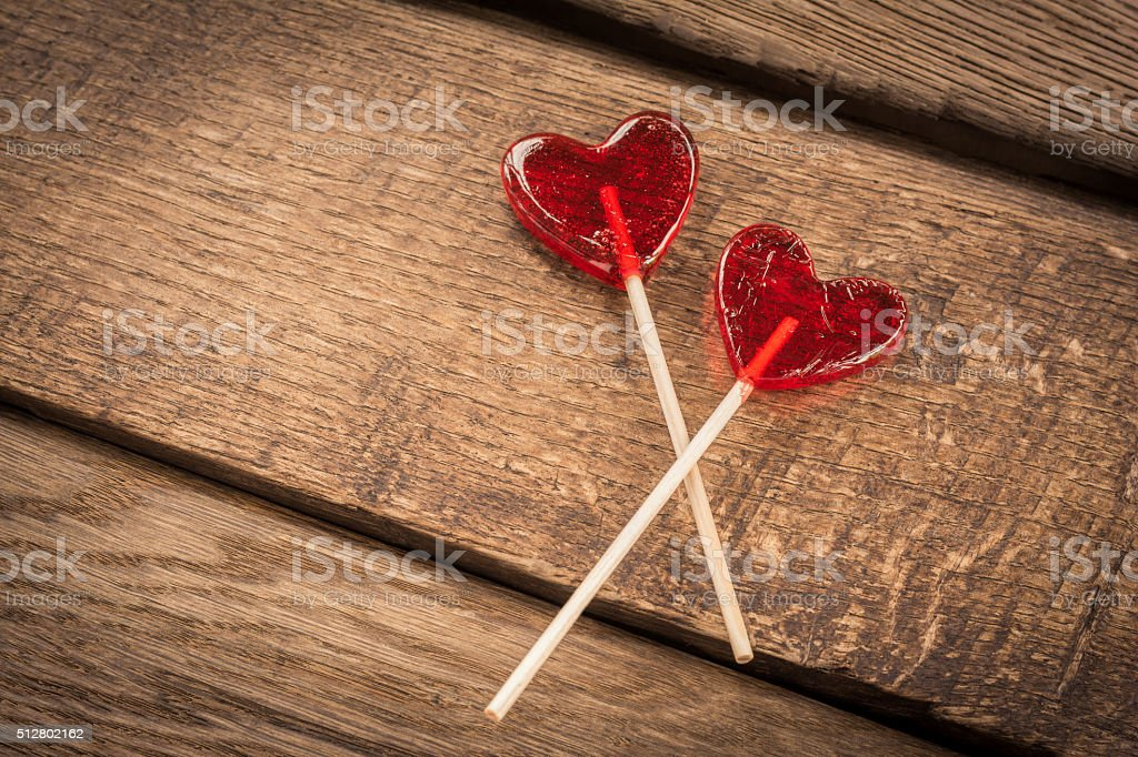Love concept. Red hearts lollipops on wooden background stock photo