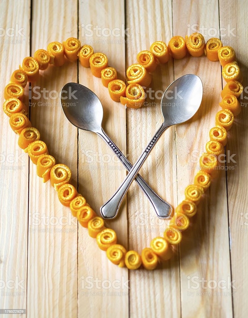 Love heart from orange peels with crossed spoons royalty-free stock photo