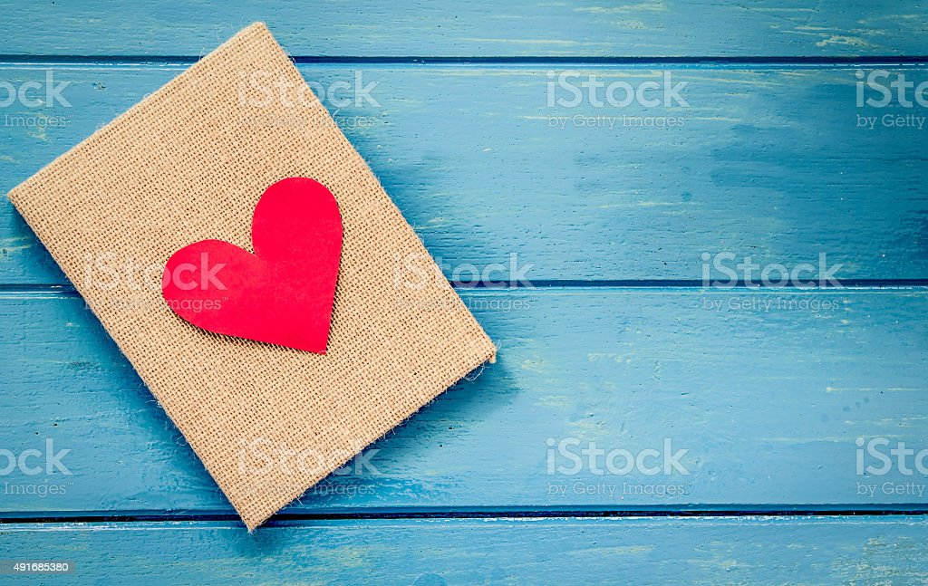 love heart on notebook on blue wooden table stock photo