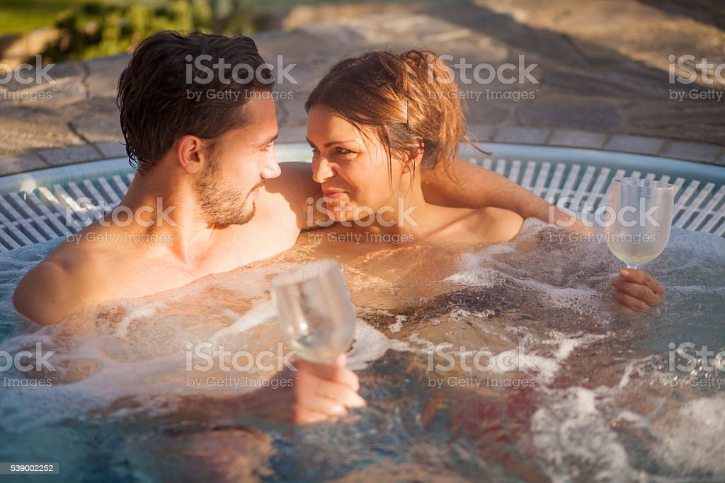 Hot tub in wooden environment with steam in the air. Young couple...