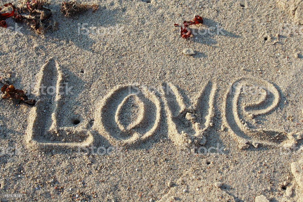 Love in sand - word of emotion stock photo