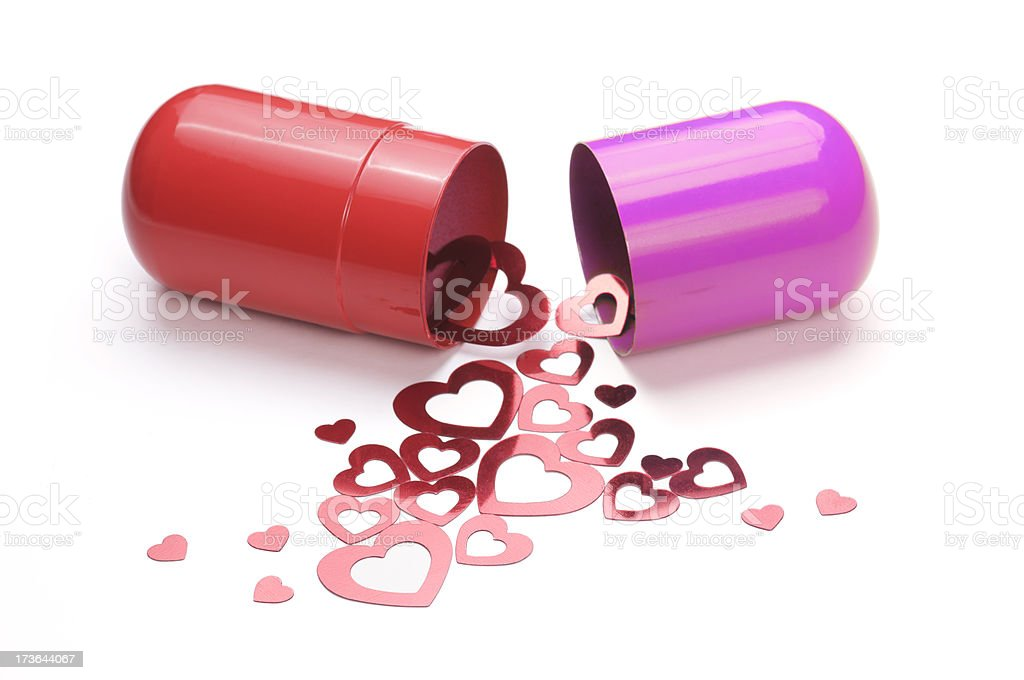 Love Is the Drug Hearts Spilling from Capsule White Background royalty-free stock photo
