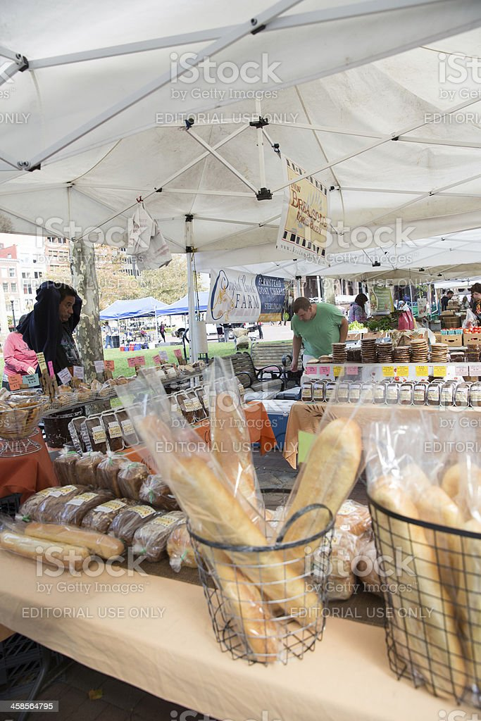 People are purchasing breads and cakes at an open air market in...