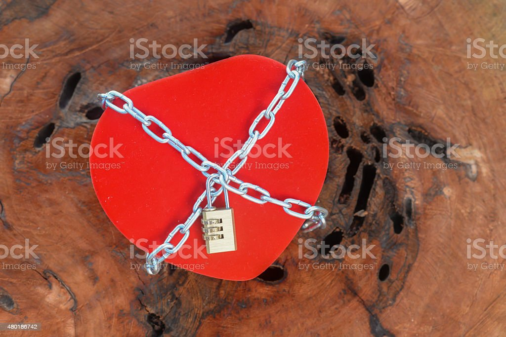love locked heart with chains on wood background stock photo