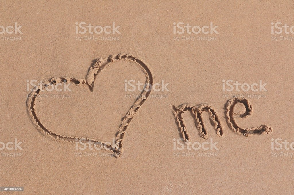 Love me written on sand on a beach stock photo