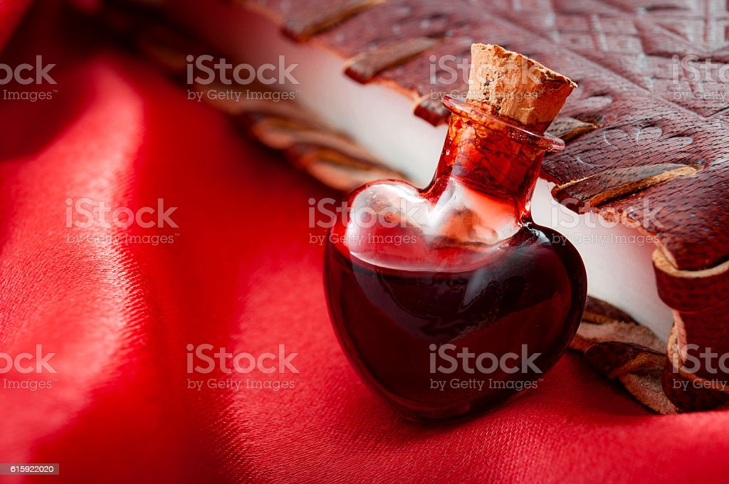 Love potion leaning on a book of spells stock photo