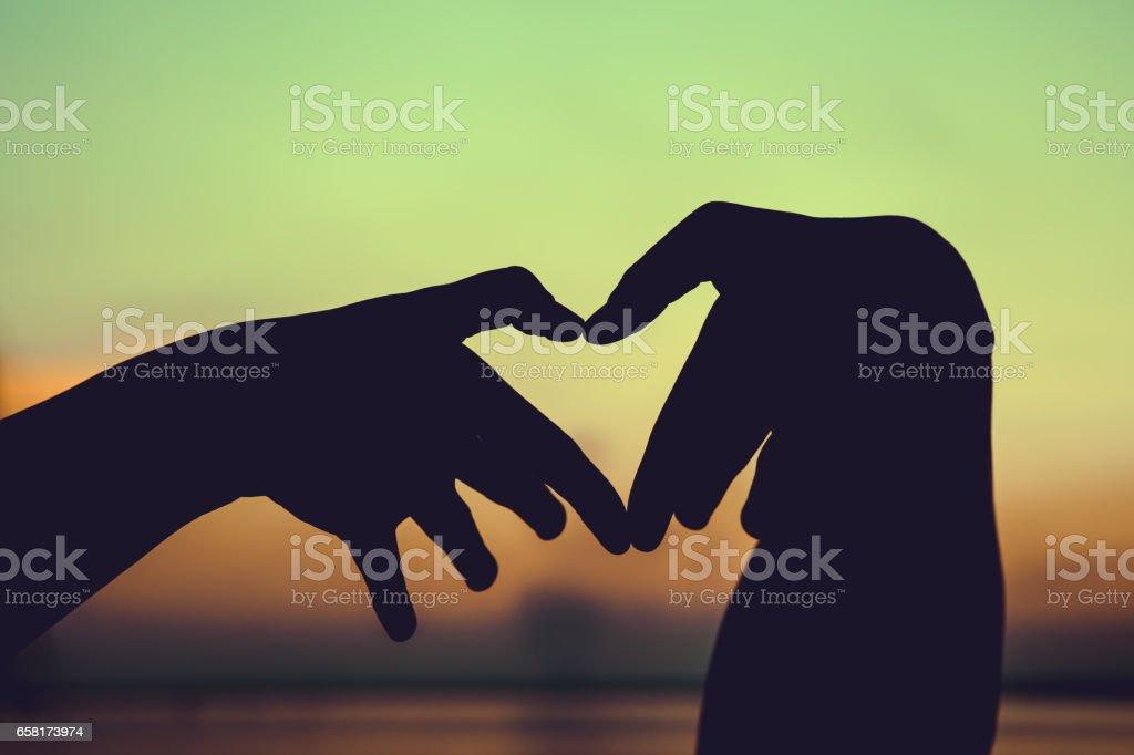 Love shape hand silhouette on sky background. stock photo