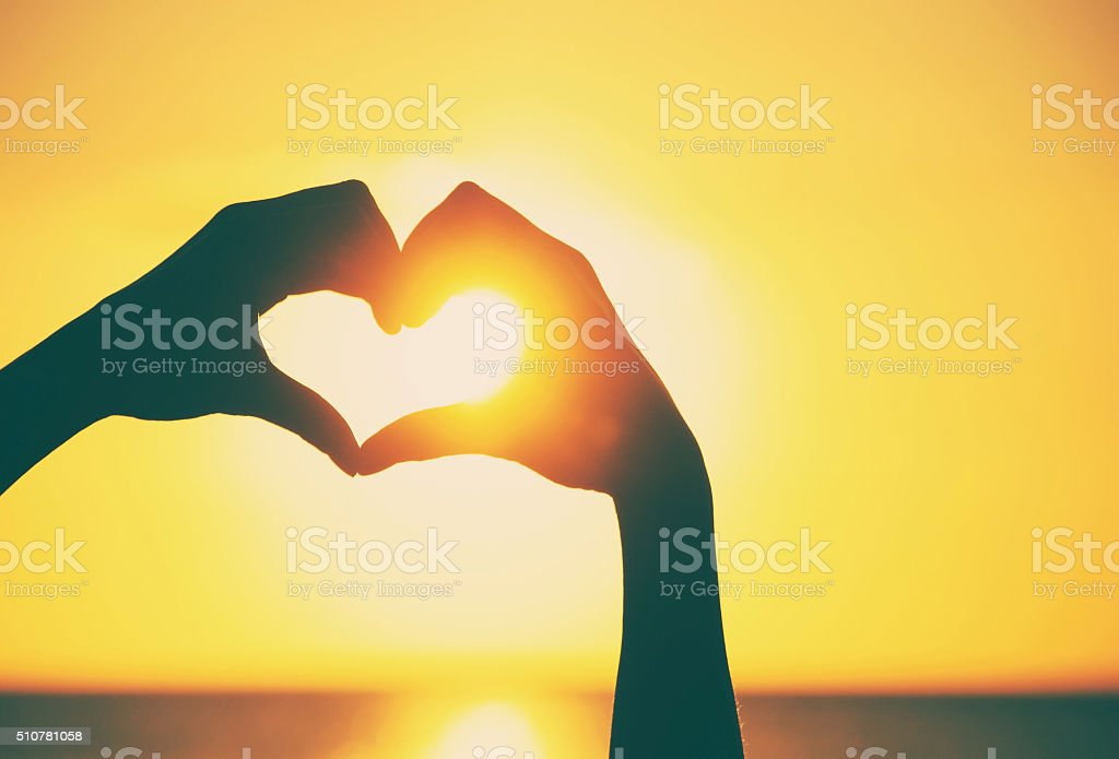 Love shape hands silhouette during sunset stock photo