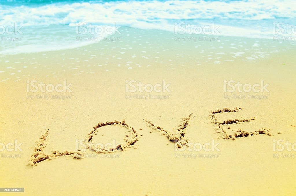 love text drawn on sanded beach stock photo