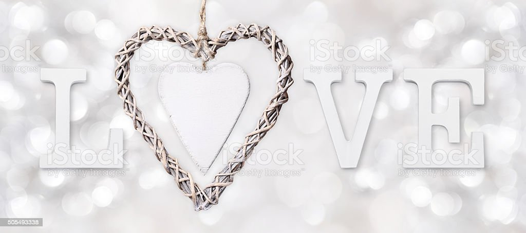 love text with heart of woven wood on silver blurred stock photo