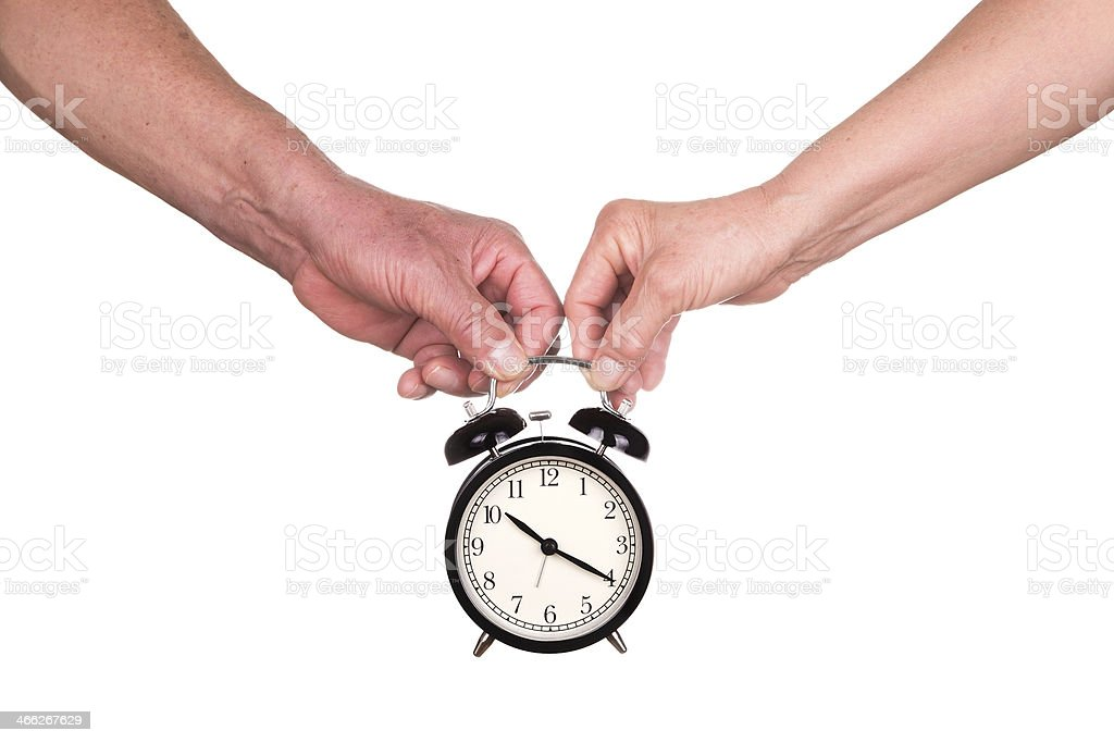 love time:senior couple holding clock ioslated on white background stock photo