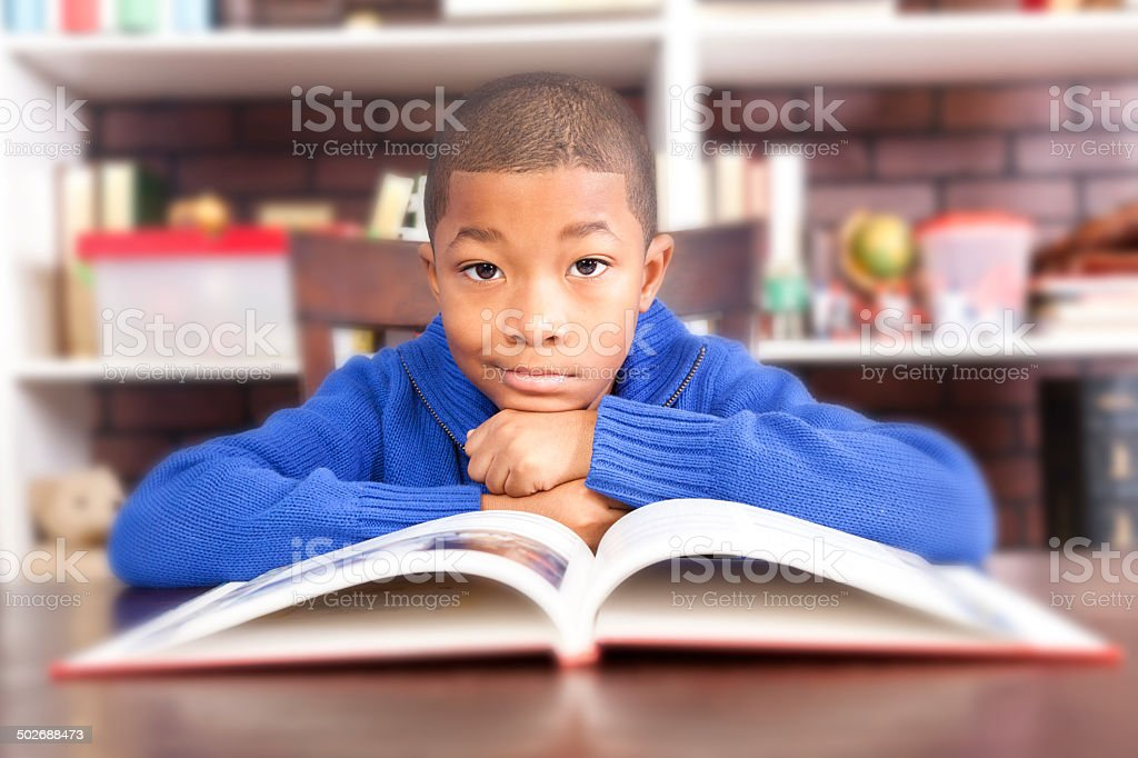 Love to read! African descent boy enjoys reading at school. royalty-free stock photo