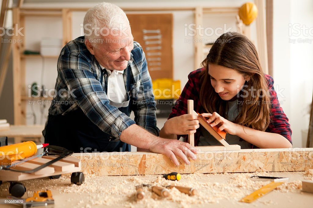 Love to spend time with grandpa at woodshop stock photo
