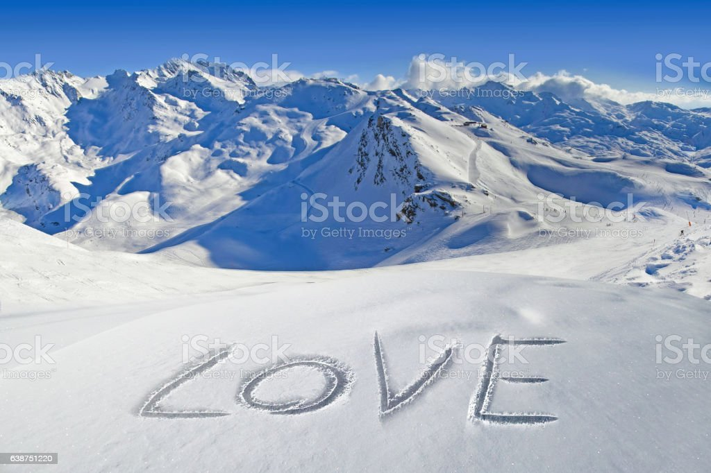 Love written in the snow, mountain landscape in the background stock photo