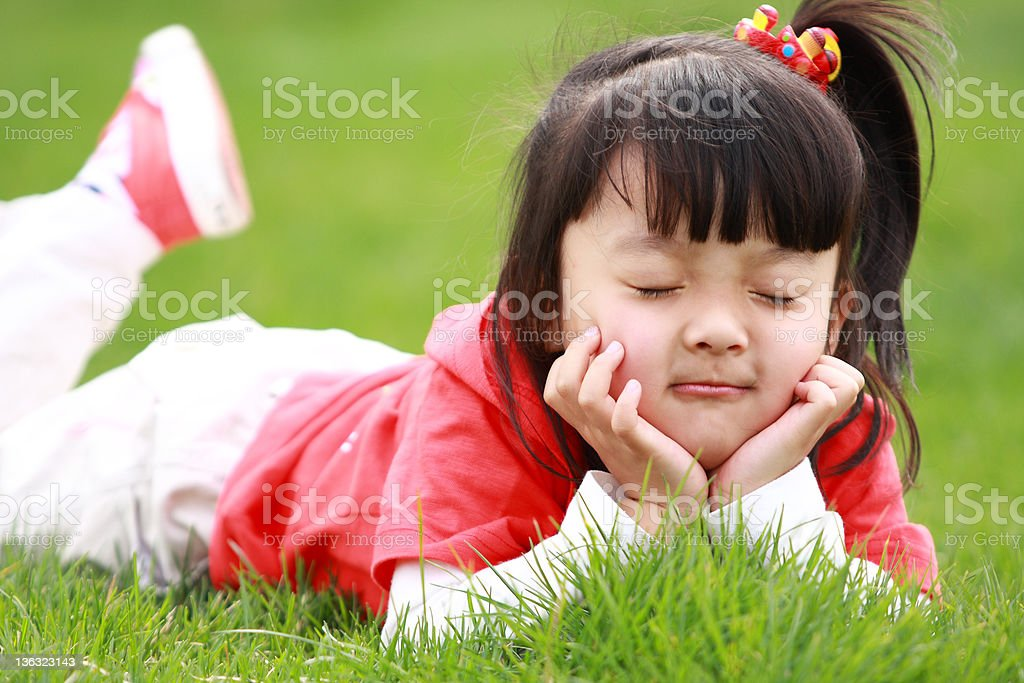 lovely asian little girl laying on the grassland royalty-free stock photo