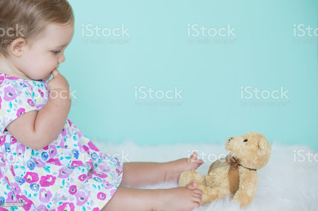 Lovely baby girl playing with teddy bear stock photo