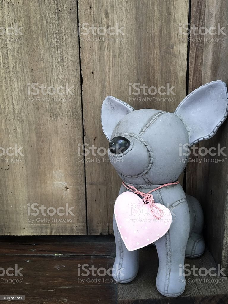 lovely baby gray dog doll standing on the wooden floor royalty-free stock photo