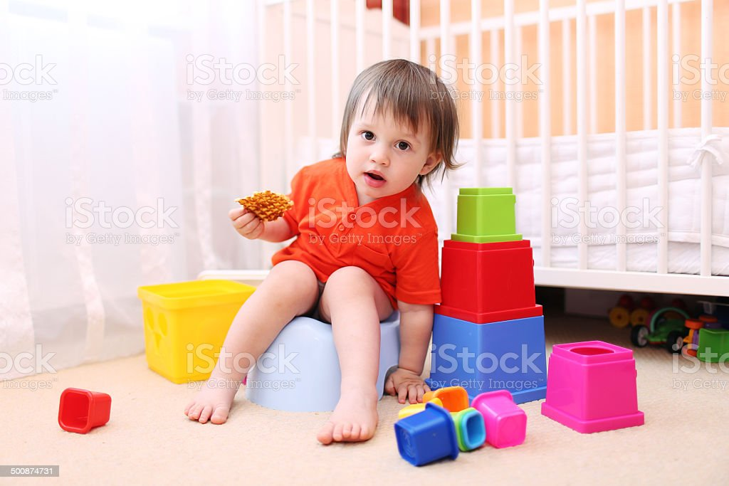 lovely baby sitting on potty stock photo