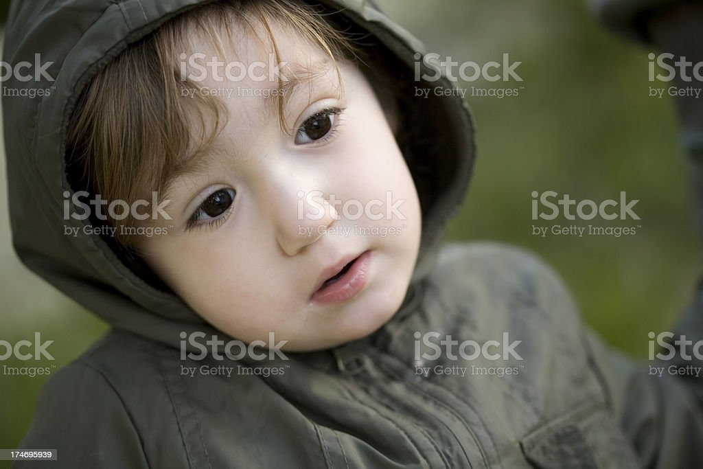 Lovely baby with green coat looking stock photo