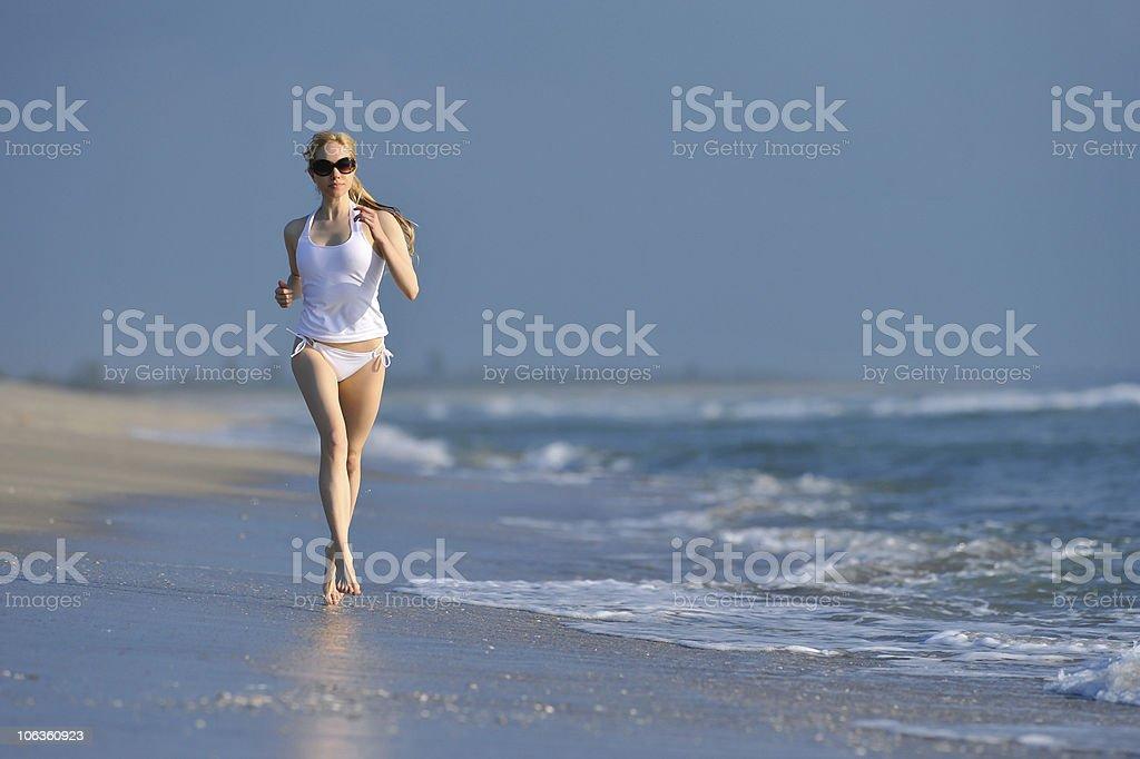 lovely blond female running on beach stock photo