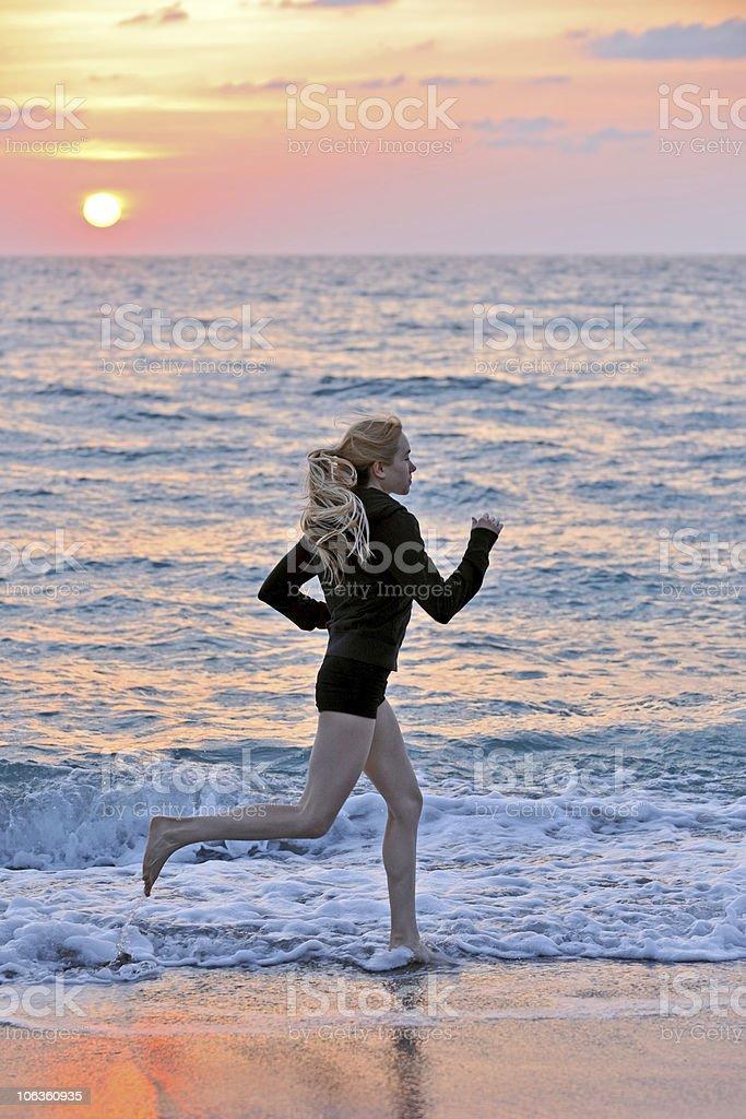 lovely  blonde female jogging beach at sunrise stock photo