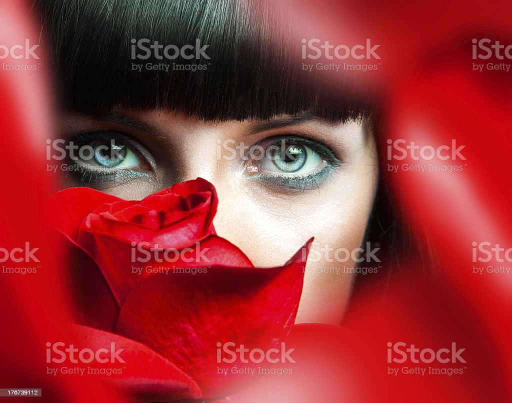 Lovely brunette behind red rose in studio royalty-free stock photo