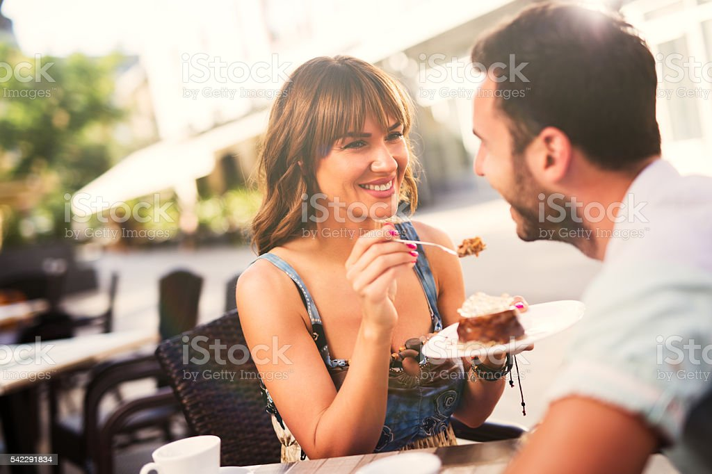 Lovely couple enjoying dessert in cafe . stock photo