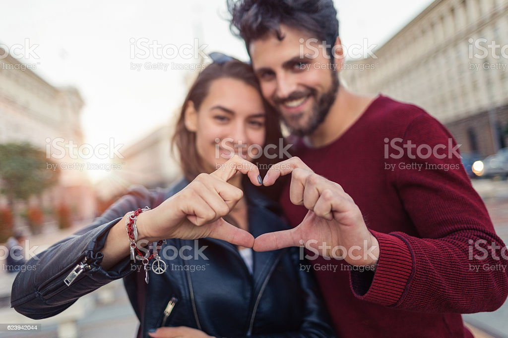 Lovely couple making heart shaped sign stock photo